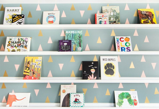 Cute wall with triangle decals and front facing bookshelves