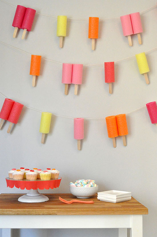 Popsicle garland - made of chopped up pool noodles and giant popsicle sticks!