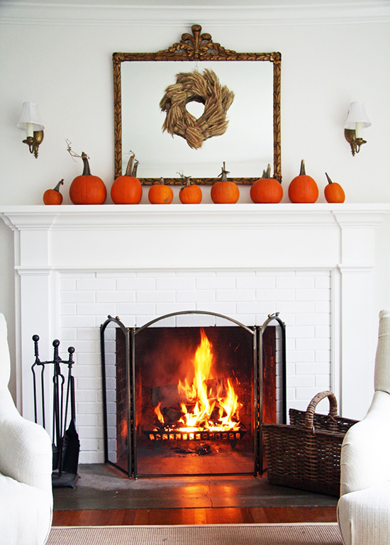 Pumpkins lined up on the mantel