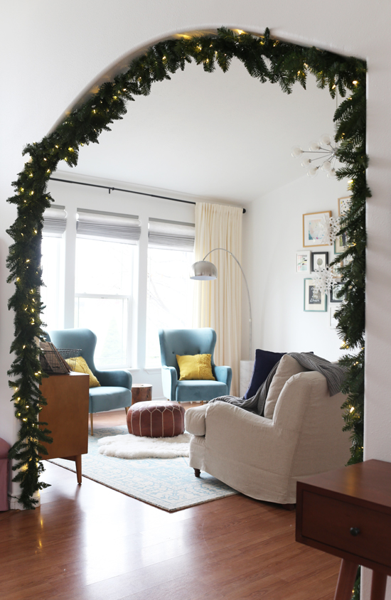 Hang Christmas garland and lights in archway